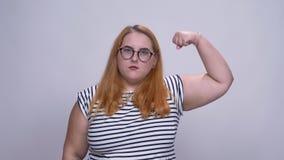 Zwaarlijvig Kaukasisch roodharig meisje die machtsteken met vertrouwen tonen die een voorzijde van grijze achtergrond zich binnen stock footage