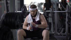 Zwaarlijvig mannelijk drinkwater na barbelloefening, die aquaevenwicht, dieet herstellen stock video