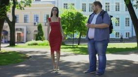 Zwaarlijvig mannetje die droevig vrij slanke dame in kleding, verschijningsonzekerheden bekijken stock video