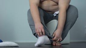 Zwaarlijvig mannetje die nauwelijks sokken, gebrek zetten aan fysische activiteit, sedentaire levensstijl stock footage