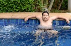 Zwaarlijvige jongen die genietend van hete ton ontspant stock afbeelding