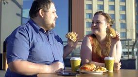 Zwaarlijvige man en vrouw die burgers delen tijdens romantische datum in openlucht, calorieën stock afbeelding