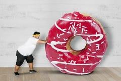 Zwaarlijvige mens die een grote doughnut duwen stock foto's