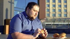 Zwaarlijvige mens die hamburger bekijken die, aarzelend te eten, gezonde levensstijl kiezen royalty-vrije stock foto