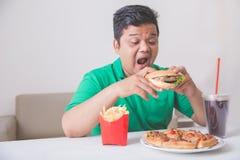 Zwaarlijvige mens die ongezonde kost eten Stock Afbeelding