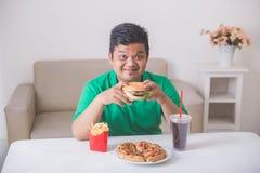 Zwaarlijvige mens die ongezonde kost eten Royalty-vrije Stock Fotografie