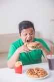 Zwaarlijvige mens die ongezonde kost eten Stock Afbeeldingen
