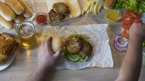 Zwaarlijvige mens die vettige gebraden karbonades toevoegen aan zijn hamburger, het ongezonde eten, hoogste mening stock video