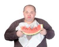 Zwaarlijvige mens die watermeloen eet Stock Foto