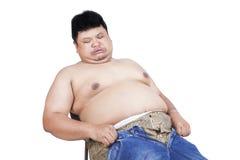 Zwaarlijvige mens die zijn oude jeans proberen te dragen Stock Foto's