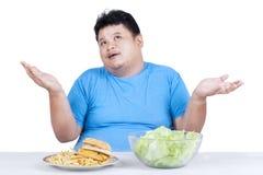 Zwaarlijvige mens met twee soorten voedsel 1 Stock Fotografie