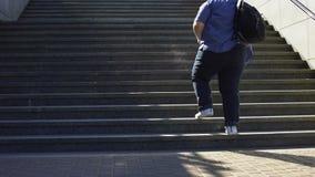 Zwaarlijvige student het lopen treden aan herberg, slecht gezondheidsprobleem op jonge leeftijd stock video