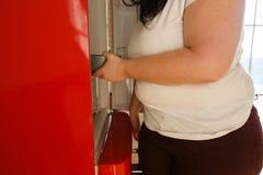 Zwaarlijvige vrouw die zich in koelkast werpen die snack zoeken stock fotografie
