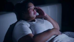 Zwaarlijvige vrouw met slapeloosheidszitting op bed stock videobeelden