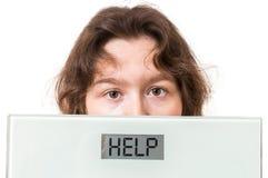 Zwaarlijvigheidsconcept De te zware vrouw houdt schalen met geschreven hulp Stock Foto
