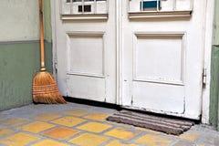 Zwabber bij de witte houten deur op vloer Stock Foto's