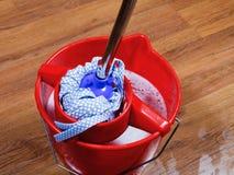 Zwabber in rode emmer met water Stock Afbeelding