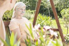 Zwak bejaarde tijdens behandeling in de het ziekenhuis` s tuin stock foto's