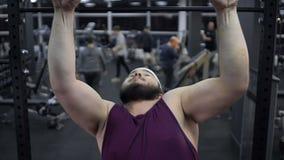 Zwak zwaarlijvig mannetje die in gymnastiek, gebrek aan zelfvertrouwen, onzekerheden proberen uit te trekken stock video