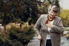 Zwakke hogere vrouw die met wandelstok op hulp tijdens ademnoodaanval wachten stock fotografie