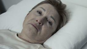 Zwakke schreeuwende dame die in bed liggen en camera, armenhuiscentrum, wanhoop bekijken stock footage