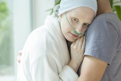 Zwakke vrouw die met kanker haar echtgenoot koesteren tijdens chemotherapie stock foto's