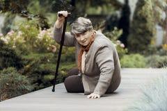 Zwakke vrouw die met wandelstok op hulp na ademnoodaanval wachten stock afbeeldingen