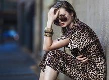 Zwakke vrouwenzitting in de stad en het dragen van een luipaard-huid kleding Stock Fotografie