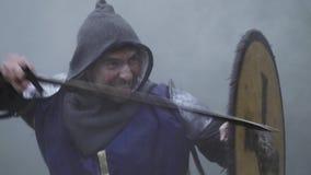 Zwalcza w dymu, wojownik w błękitnym opancerzeniu walczy z jego kordzikiem zdjęcie wideo
