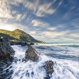 Zwalnia żaluzi fotografię fala łama na skałach w Corsica Obraz Royalty Free