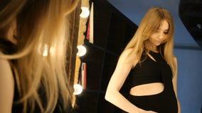 Zwanger bewondert de buik in de spiegel stock videobeelden