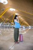 Zwanger bij telefoon in luchthaven Stock Foto