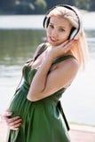 Zwanger blondemeisje met hoofdtelefoons Stock Foto's