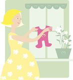 Zwanger geniet baby van kleding Stock Foto's