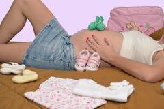 Zwanger mamma, babykleren Stock Fotografie