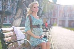 Zwanger meisje die rond het stadspark lopen in de vroege lente Stock Foto's