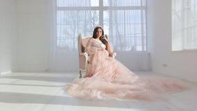 Zwanger meisje in een luxueuze roze kleding stock video