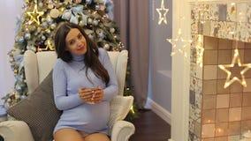 Zwanger meisje met thee als voorzitter op nieuwe jaar` s vooravond stock videobeelden