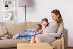 Zwanger vrouw en meisje die aan baby in buik spreken Stock Fotografie