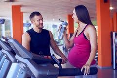 Zwanger vrouwen drinkwater terwijl het spreken aan persoonlijke trainer royalty-vrije stock foto