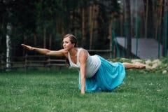 Zwanger yoga prenataal moederschap die verschillende oefeningen doen in het park op het gras, ademhaling, het uitrekken zich, sta royalty-vrije stock fotografie