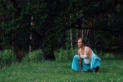 Zwanger yoga prenataal moederschap die verschillende oefeningen doen in het park op het gras, ademhaling, het uitrekken zich, sta royalty-vrije stock foto