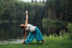 Zwanger yoga prenataal moederschap die verschillende oefeningen doen in het park op het gras, ademhaling, het uitrekken zich, sta stock foto