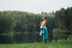 Zwanger yoga prenataal moederschap die verschillende oefeningen doen in het park op het gras, ademhaling, het uitrekken zich, sta stock fotografie