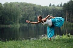 Zwanger yoga prenataal moederschap die verschillende oefeningen doen in het park op het gras, ademhaling, het uitrekken zich, sta stock foto's
