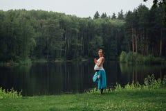 Zwanger yoga prenataal moederschap die verschillende oefeningen doen in het park op het gras, ademhaling, het uitrekken zich, sta stock afbeeldingen