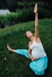 Zwanger yoga prenataal moederschap die verschillende oefeningen doen in park op het gras, ademhaling, het uitrekken zich, statica stock foto's