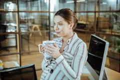 Zwangere aantrekkelijke vrouw die smakelijke warme thee in bureau drinken stock afbeelding