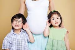 Zwangere Aziatische moeder en haar jonge geitjes Stock Foto's