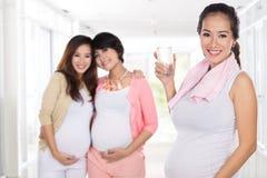 Zwangere Aziatische vrouw die een glas water na het doen van ex wat hebben stock fotografie
